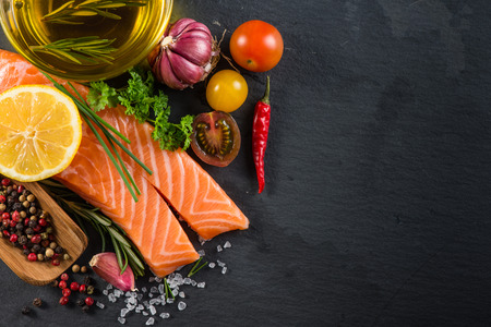 Portion of fresh salmon with spices,herbs and vegetables on black slate background