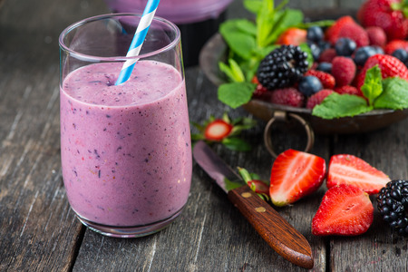 Foto de Homemade antioxidant summer fruits smoothie on rustic table - Imagen libre de derechos