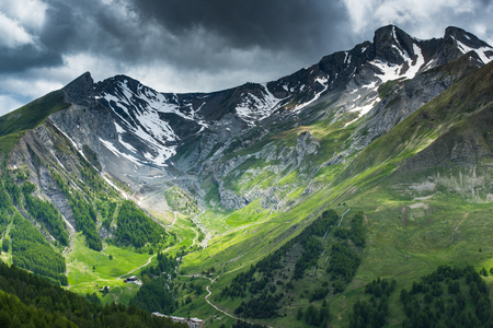 Stunning valley at foot of the French Alps with snowy peaks and thunderstorm clouds.