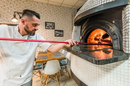 Photo pour Handsome pizzaiolo man baking pizza in woodfired oven in local pizzeria - image libre de droit