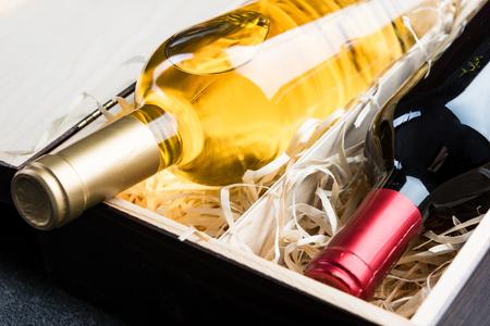 Foto de Close up view on wine bottles in wooden vintage box. - Imagen libre de derechos