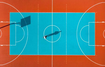 Photo pour Basketball Player, Long Shadows on Basketball Court, Creative Visual Art, Aerial Image. - image libre de droit