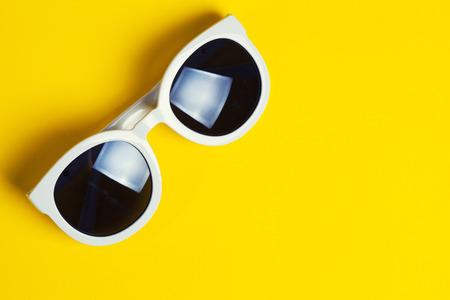 Stylish white sunglasses on yellow background