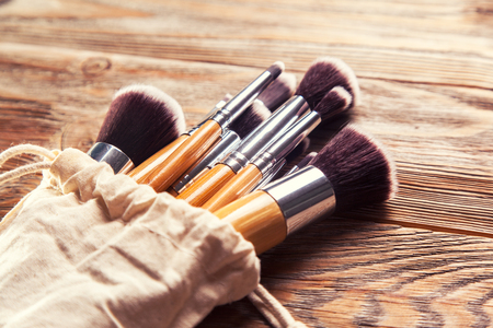 set of brushes for makeup scattered chaotically on wooden backgroundの写真素材