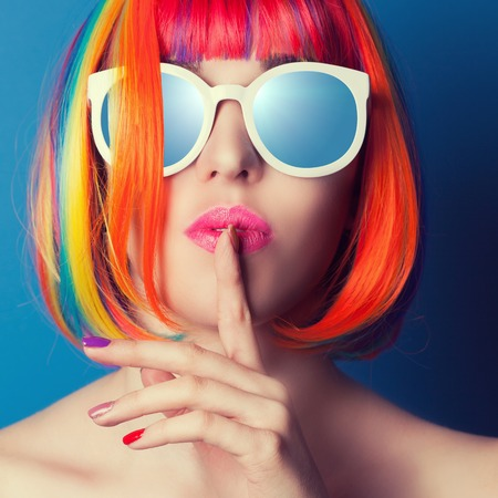 Foto de beautiful woman wearing colorful wig and white sunglasses against blue background - Imagen libre de derechos