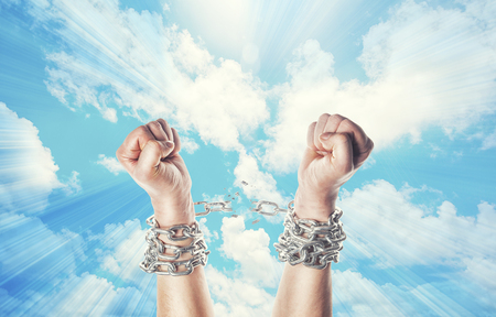 Photo pour Two hands in chains on a heavens background with a flash - image libre de droit