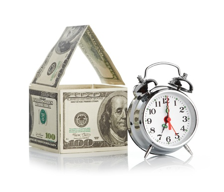 house made of dollars and alarm clock  Isolated on white background
