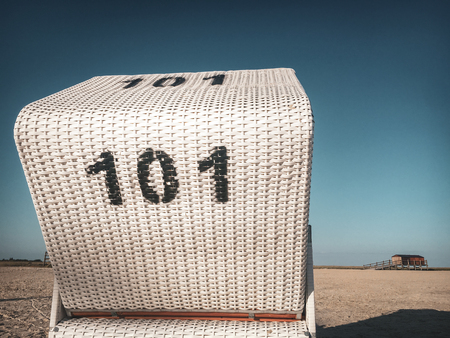 Nostalgic picture of traditional north German white beach chair with black number 101 at North Sea beach in St. Peter-Ording, Germany