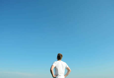 Young man in white t-shirt looking at the blue sky