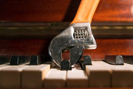 Photo for Close up of an adjustable wrench holding and pressing a piano key. Fine tuning concept.  - Royalty Free Image