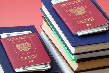 two foreign passports of Russians are on different stacks of books in the passport invested money for the trip