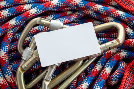 an empty business card without an inscription on the climbing equipment a rope and devices for fixing to the anchor line
