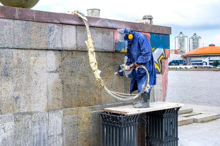 Russia, Yekaterinburg, August 14, 2019 a city utility employee removes graffiti on the wall with water. removing paint from the wall