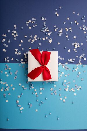 Photo pour Happy Valentine's Day card with gift, small stars and white gift with red bow on classic blue background. Holiday time concept. Mockup template. Top view - image libre de droit