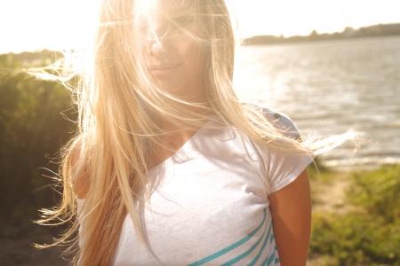 Photo pour blond girl sitting near river against sun - image libre de droit
