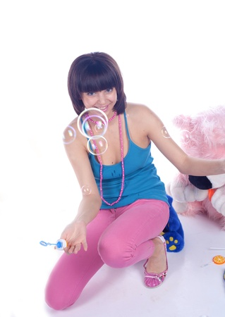 young beautiful brunette and soap bubble on white
