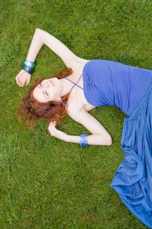 redhead women on grass daydreaming