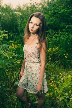 Beautiful Young Woman standing in Meadow of Flowers  Enjoying Nature