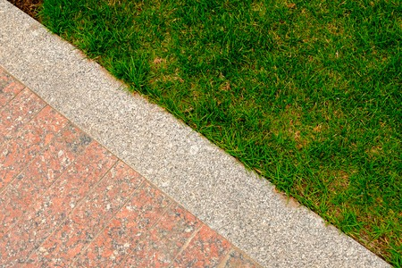 Old red and gray granite pavement and grass in garden decorative texture, line dividing nature and civilization, concept.