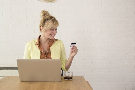 Photo for Happy excited woman using credit card and laptop for online shopping. She is sitting at table at home. - Royalty Free Image