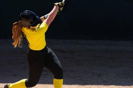 Foto de A Female Baseball Player is Swinging Her Bat for the Fences In Tournament Play. - Imagen libre de derechos
