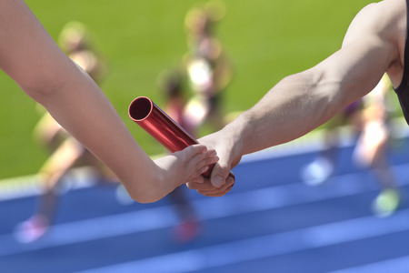 Male  relay runner hands over the red baton to female runner