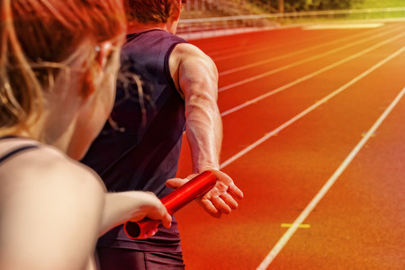Relay race handing over from woman to man