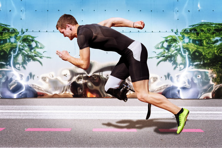 Explosive sprint of male athlete on road surface with strong reflecting metal background. Filtered version.の写真素材