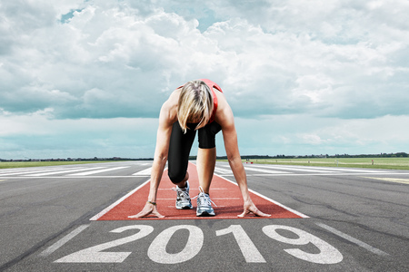 Photo pour Female runner waits for her start at an airport runway. In the foreground the painted date 2019 symbolises the year. - image libre de droit