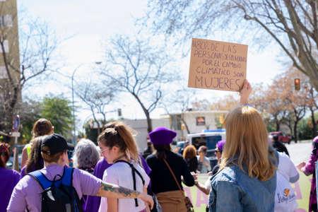 Palma de Mallorca, Spain - March 08, 2020: International Women's Day. Blonde girl with a banner in the feminist protest, in the banner: El 80% DE LAS PERSONAS DESPLAZADAS POR EL CAMBIO CLIMATICO SON MUJERES.