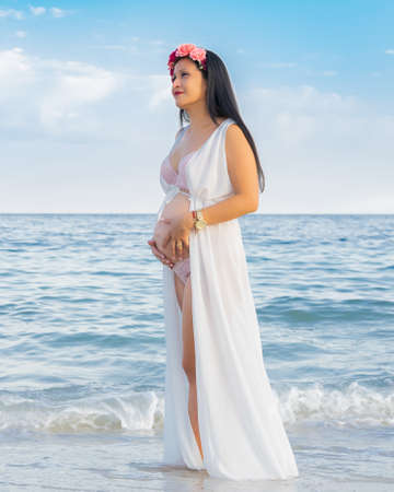 Foto de Health during pregnancy. Gorgeous pregnant young Latin girl lovingly touching her belly on the seashore - Imagen libre de derechos