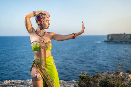 Foto de Young and beautiful woman with tattoos wearing African ethnic clothes and hugging herself in front of the sea - Imagen libre de derechos