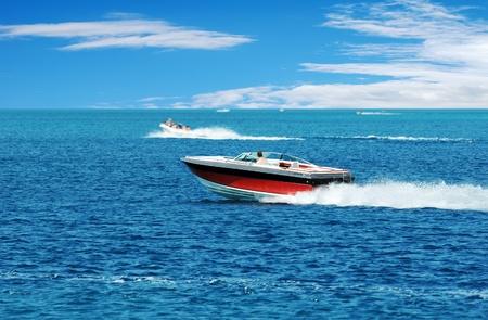 Photo pour red power boat with blue sky and clouds - image libre de droit