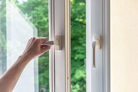 Photo pour woman hand opens a plastic window for airing. Modern plastic windows. - image libre de droit