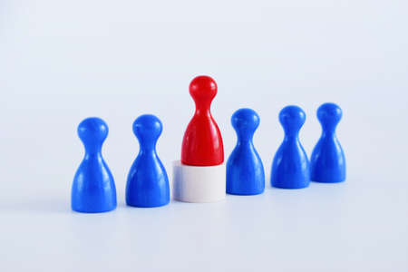 Foto de Wooden figures on white background. The red man comes out with a team of workers. The concept of choosing a new leader. Choice of person. Hiring and recruiting. Human resource management. - Imagen libre de derechos