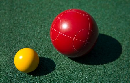 Closeup of a red bocce ball and a yellow palino