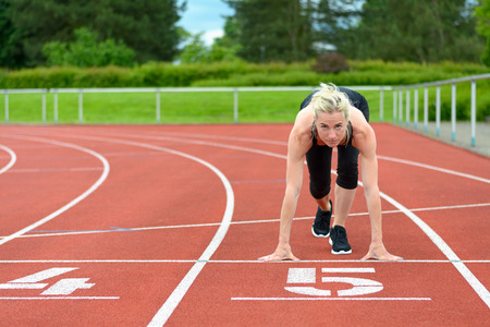 Athletic woman crouched down in the starter position on a race track at a sporting venue looking up at the camera with determination