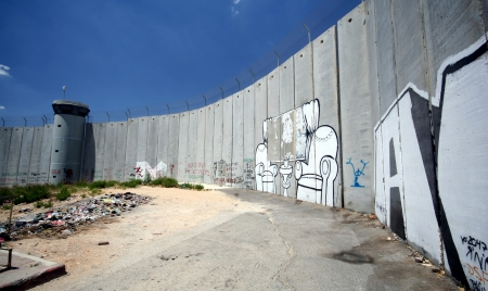 The Israeli separation wall juts into the Palestinian West Bank town of Bethlehem, along the border of Aida Refugee Camp, covered with graffiti by protesters of the barrier