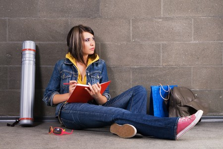 Pretty student sitting near the wall and writing at notebook