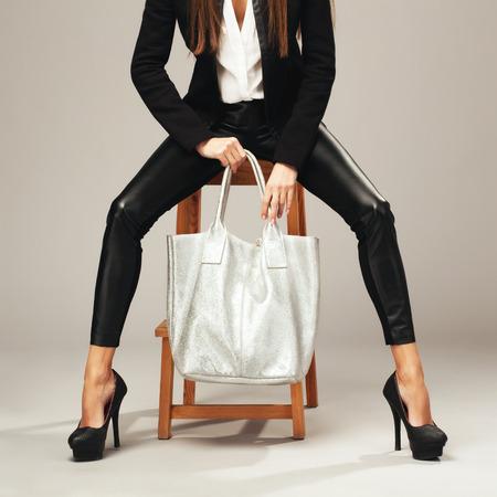 Photo pour Elegant woman with a silver fashion bag - image libre de droit