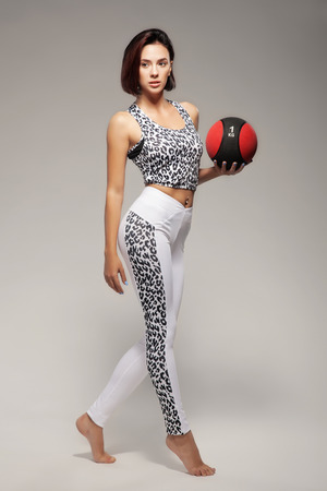 Beautiful sporty woman with a ball