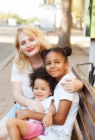 Photo pour Outdoor portrait of young beautiful mother with her lovely daughters - image libre de droit