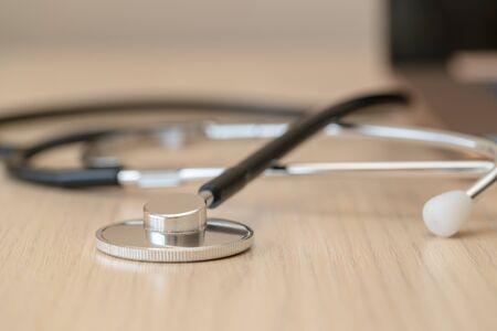 Photo pour Macro black stethoscope on light brown desk, close up picture. Laptop is on the background. Horizontal image - image libre de droit