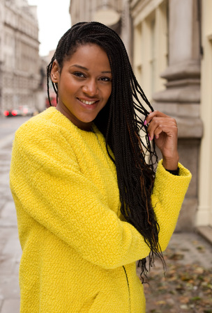 beautiful african american woman wearing a colourful yellow jumper.