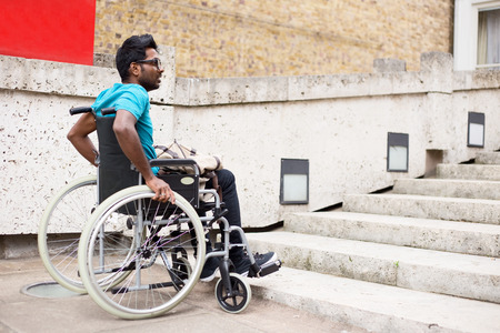 disabled man in a wheelchair waiting at the bottom of steps