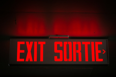 Red exit sign in English and French reflecting on concrete ceiling.