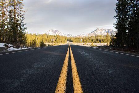 Photo pour Yellow lines on roadway leading towards mountains - image libre de droit