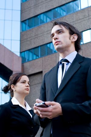 well dressed business man standing next to a young beautiful business woman using a palmtop (PDA)