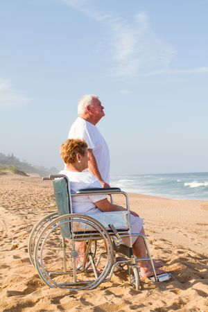 senior couple on beach - wife in wheelchairの写真素材