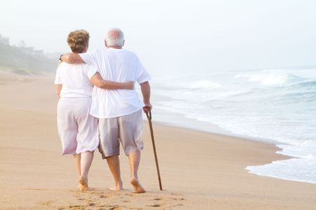 elderly couple strolling on beach